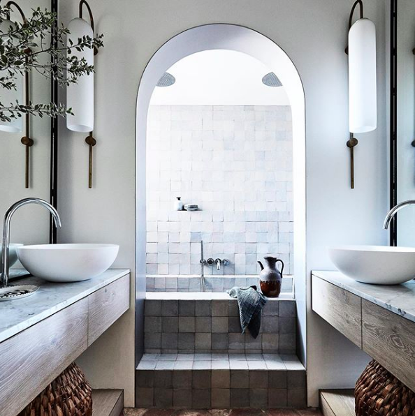 Bathrooms that don't use white tiles arch doorway and grey tiles