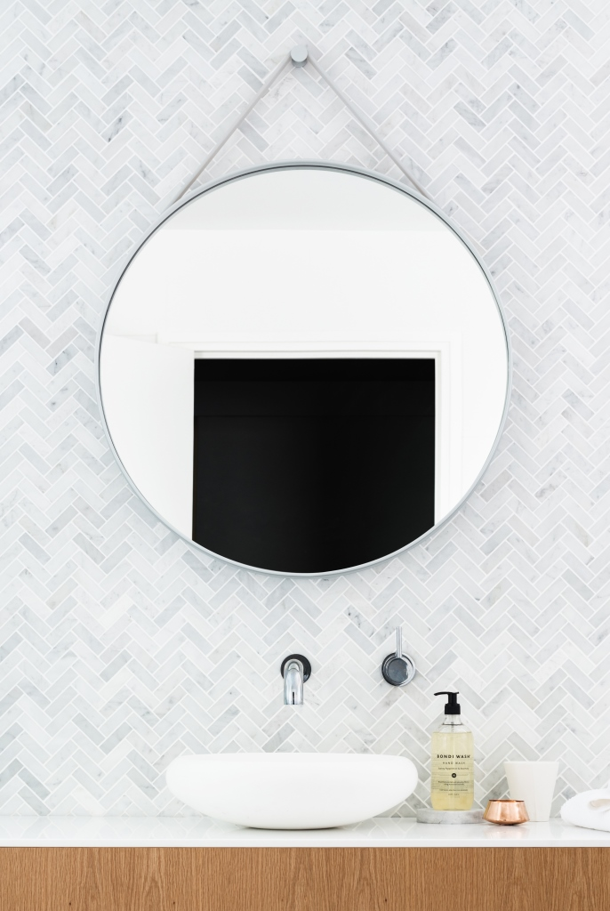Round mirror against marble tile wall