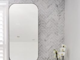 Mirror against marble herringbone wall