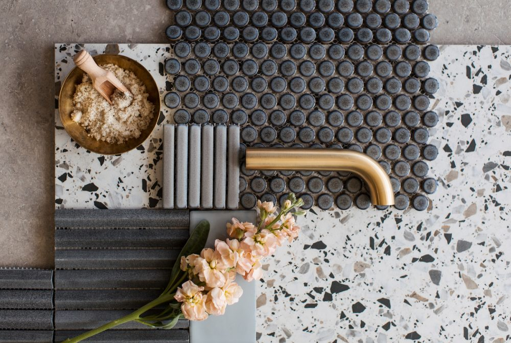 Tapware and tile flatlay featuring terrazzo tile, glazed penny round tiles, kit Kat finger tiles and stone mosaics