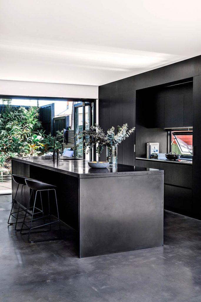 Black kitchen on polished black concrete floor
