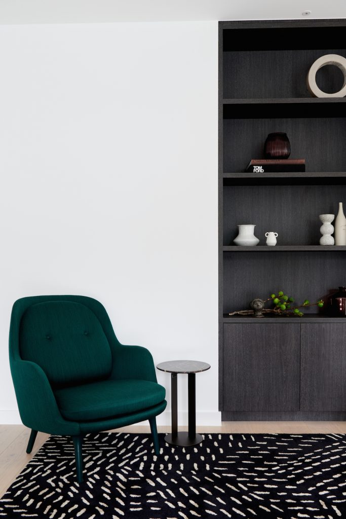 Alexi George styling lounge room with green velvet chair and bookcase in this modern home