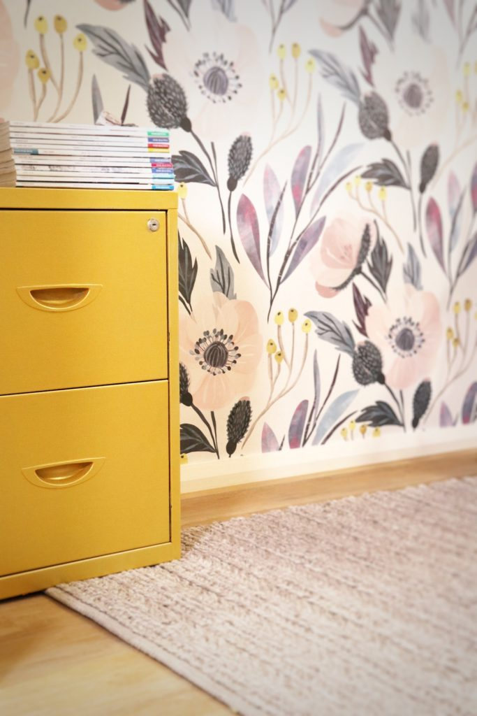 Yellow filing cabinet in wallpapered office