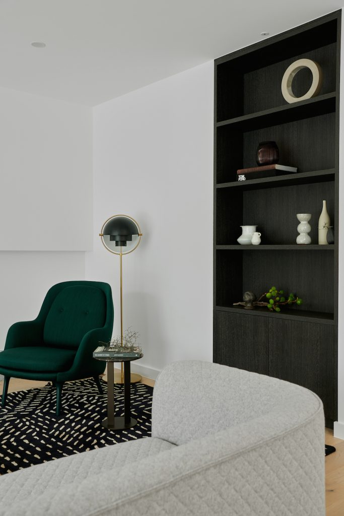 Lounge room with green velvet chair and dark veneer bookcase