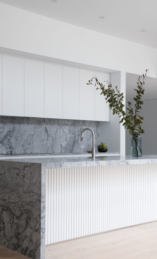 Waterfall stone island bench and white cabinets in kitchen splashbacks