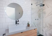 White bathroom with statement round mirror