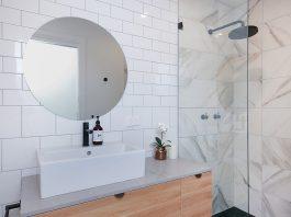 White bathroom with statement round mirror