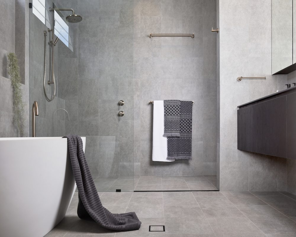 Grey floor to ceiling tiled ensuite with freestanding bath