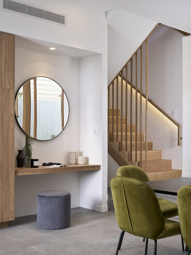 Hallway featuring round mirror and wooden balustrades modern construction