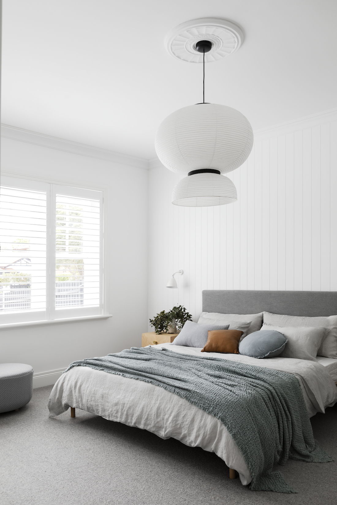 White panelled wall bedroom with statement light
