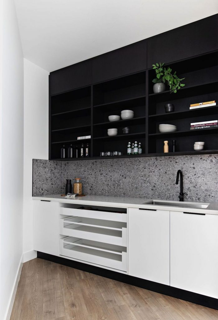 Black kitchen with open shelving and white cabinetry