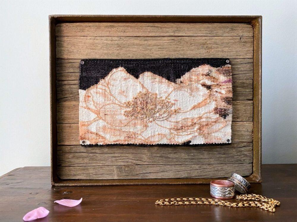 Timber frame surrounding woven floral art piece