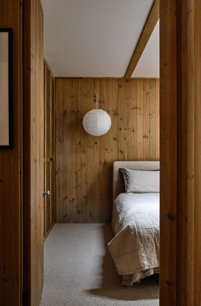 Wood panelled bedroom with paper lantern light