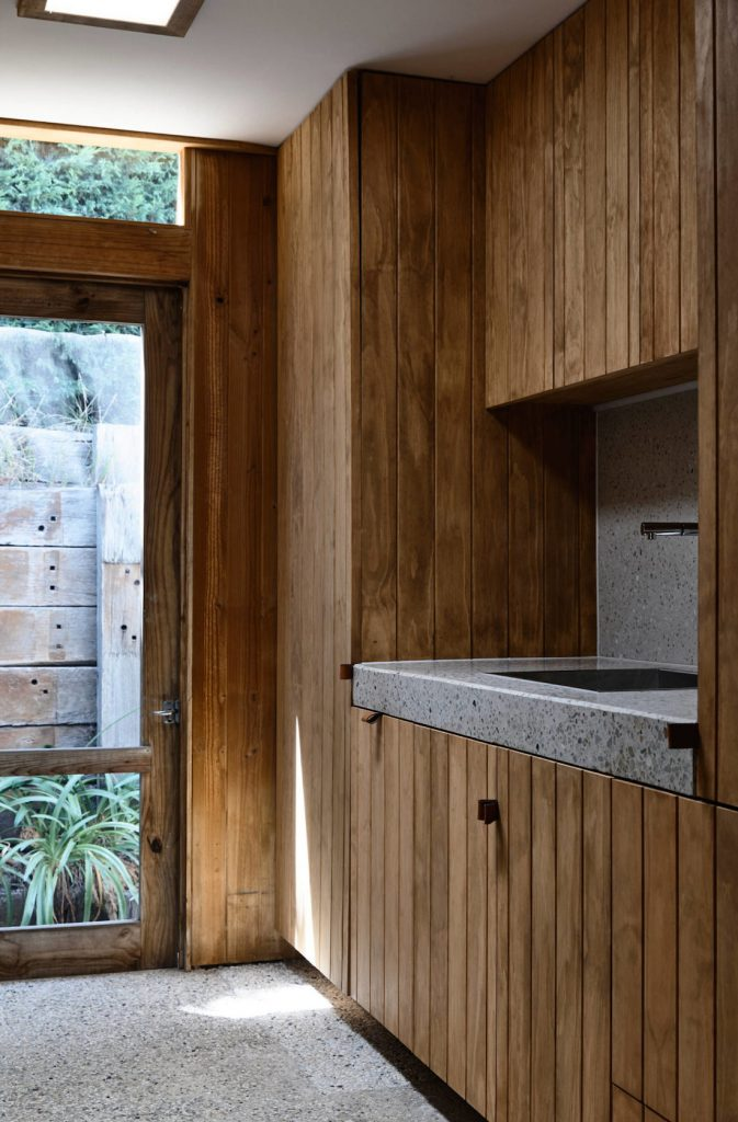 Wooden panelled laundry with terrazzo worktop