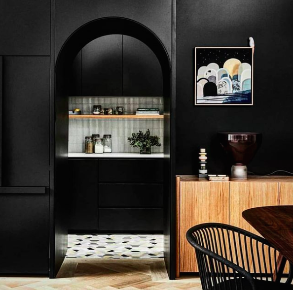 Black dining room wall with curved arch doorway