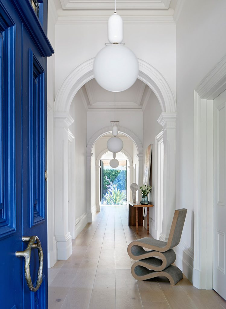 Coloured door into traditional white hallway