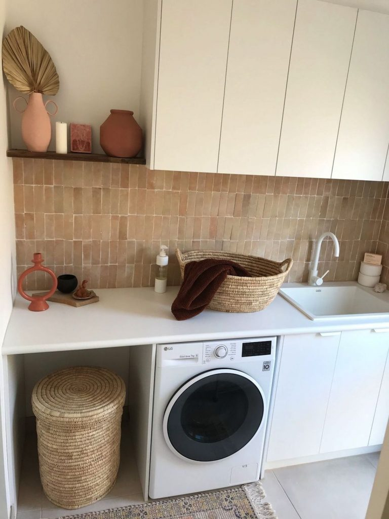 Stylish laundry with pink feature tile