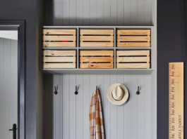 Grey mudroom with wooden boxes for storage in garage and wooden height chart