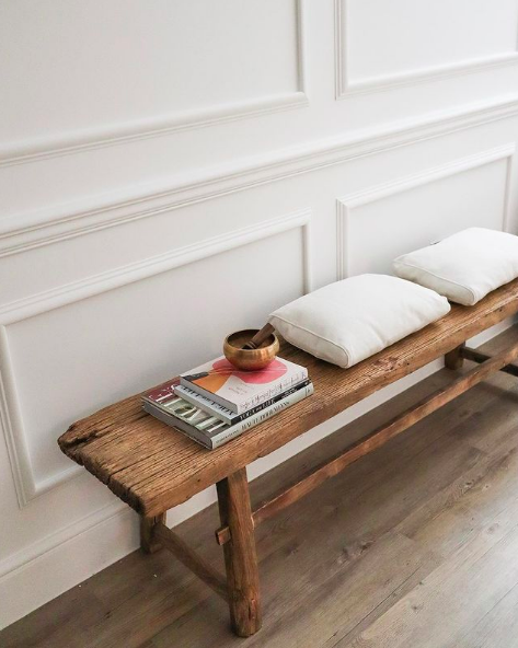 Rustic bench seat by wainscotting wall