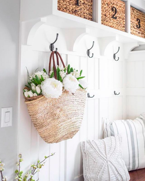 White mudroom with hooks and baskets for storage