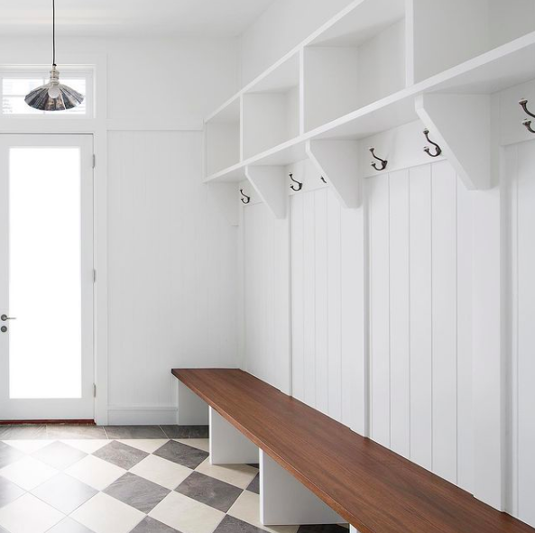 White mudroom with diamond tiles and wooden bench