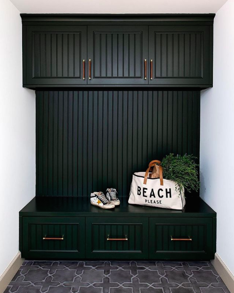 Black panelled mudroom with patterned floor