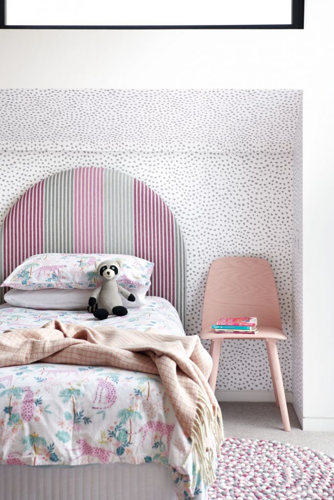 Girls bedroom with spotted wallpaper