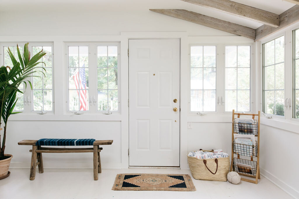 Drop zone by door of white home with rustic features