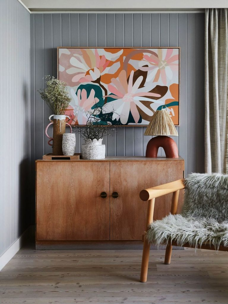 Ceramics atop a sideboard with colourful artwork and fluffy chair