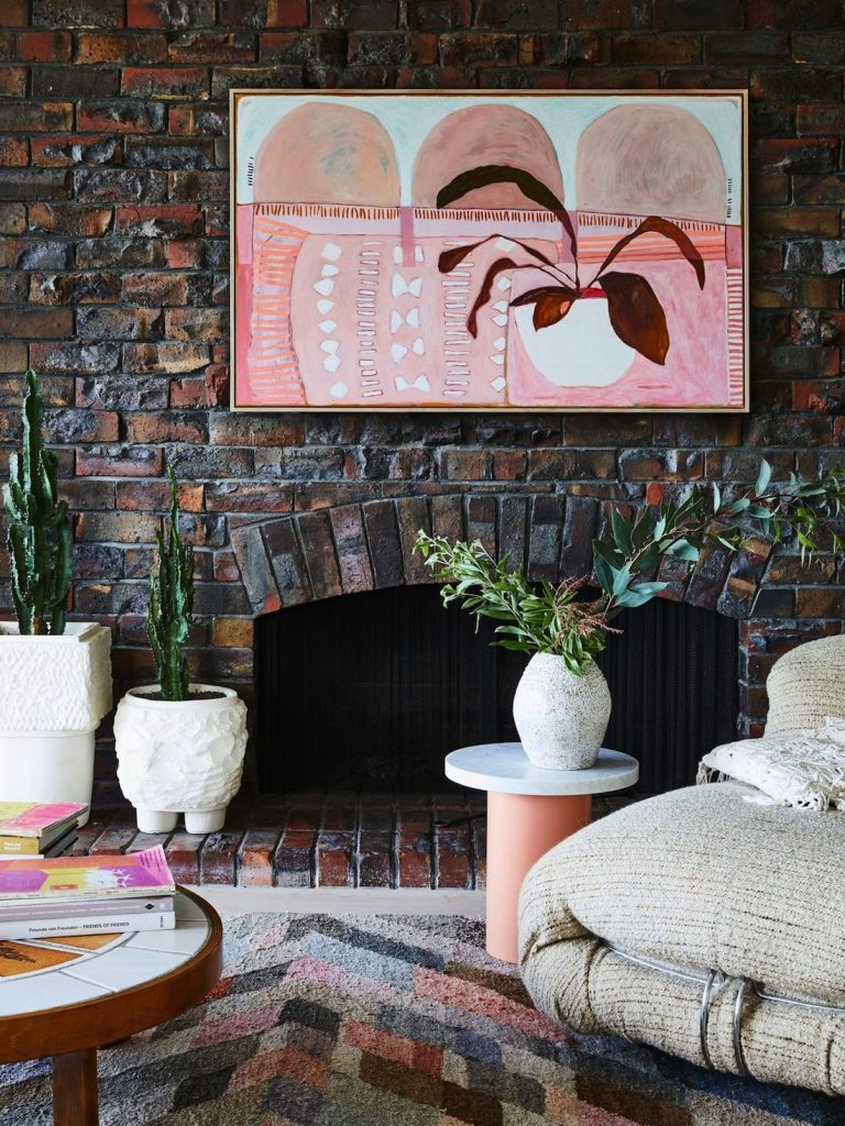 Pink artwork on brick fireplace with ceramic vase