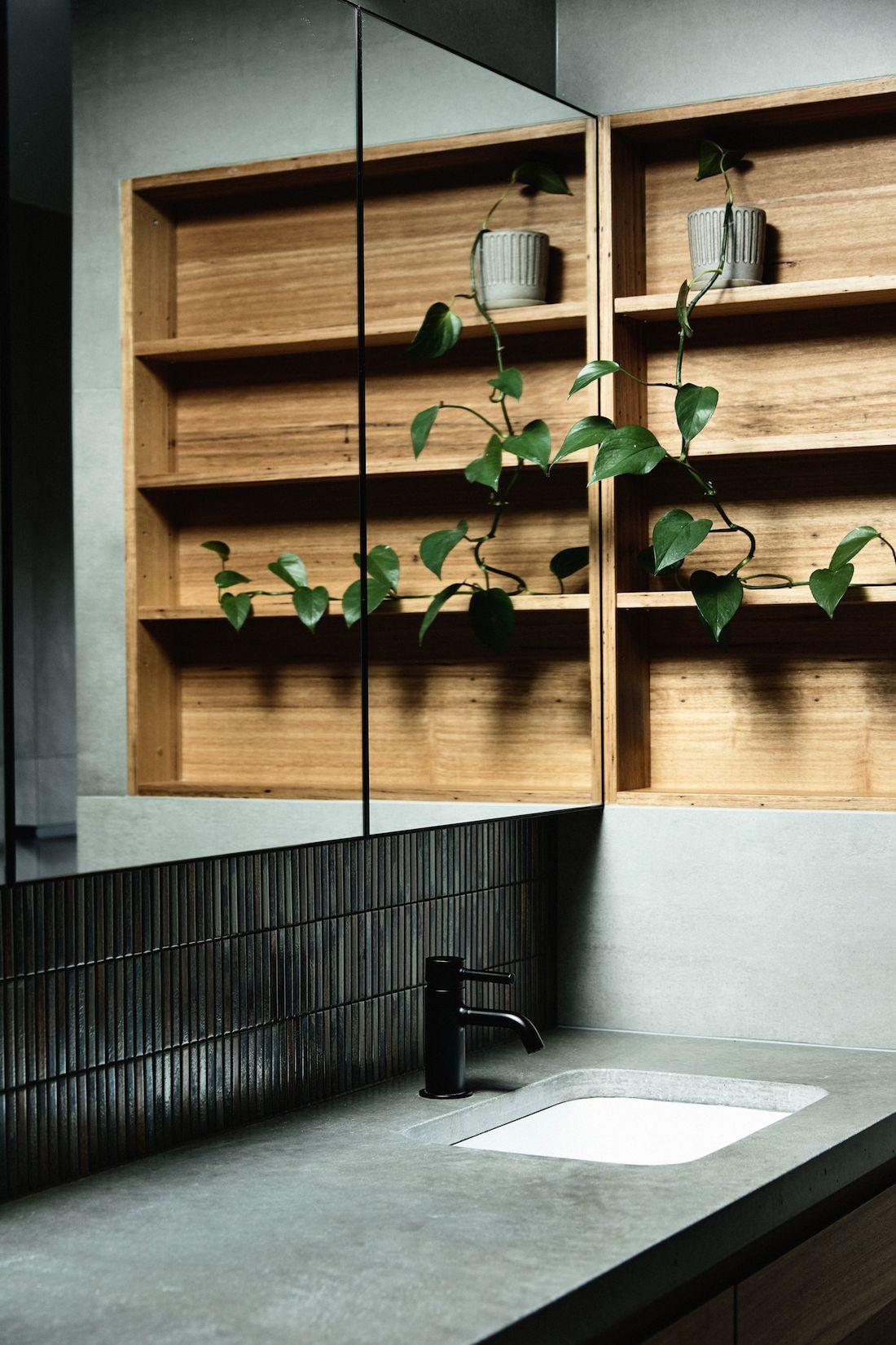 Dark tiled bathroom with timber shelving