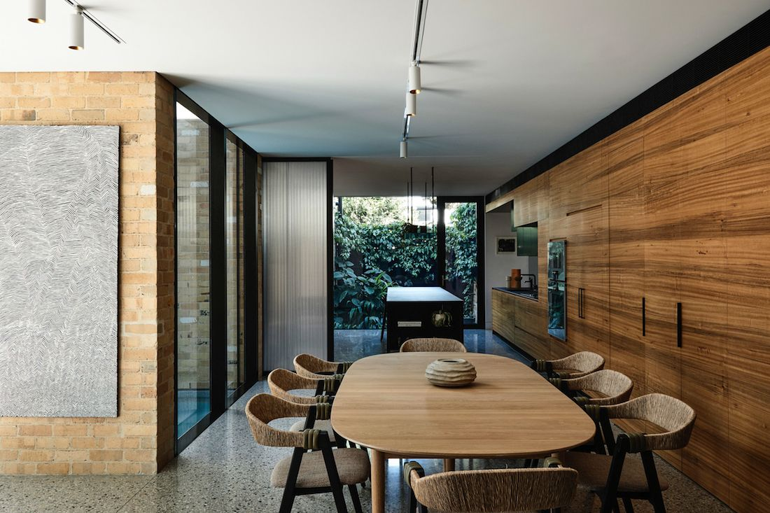 Curved timber dining table in open concept living dining kitchen