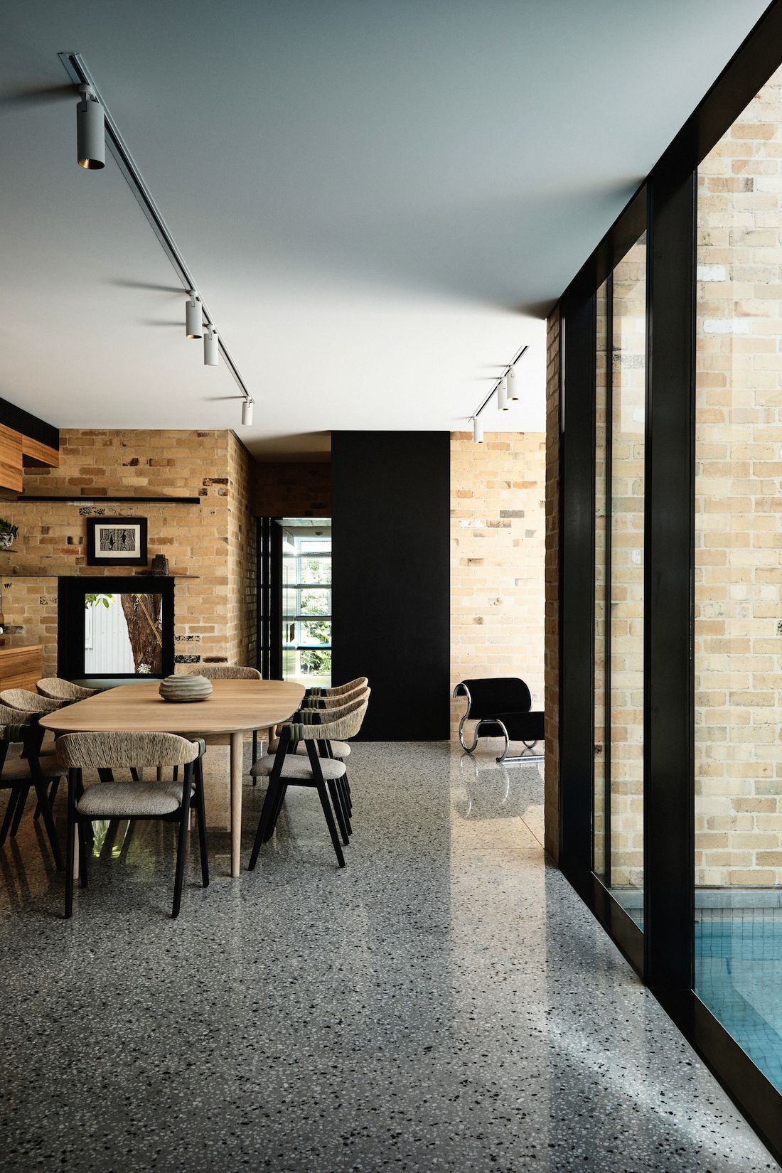Yellow brick, concrete floors and black framed doors in living dining kitchen space