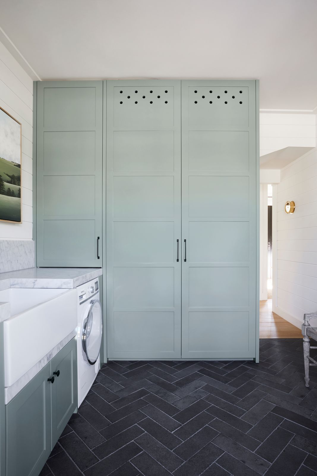 Green cabinetry in sage green and marble laundry