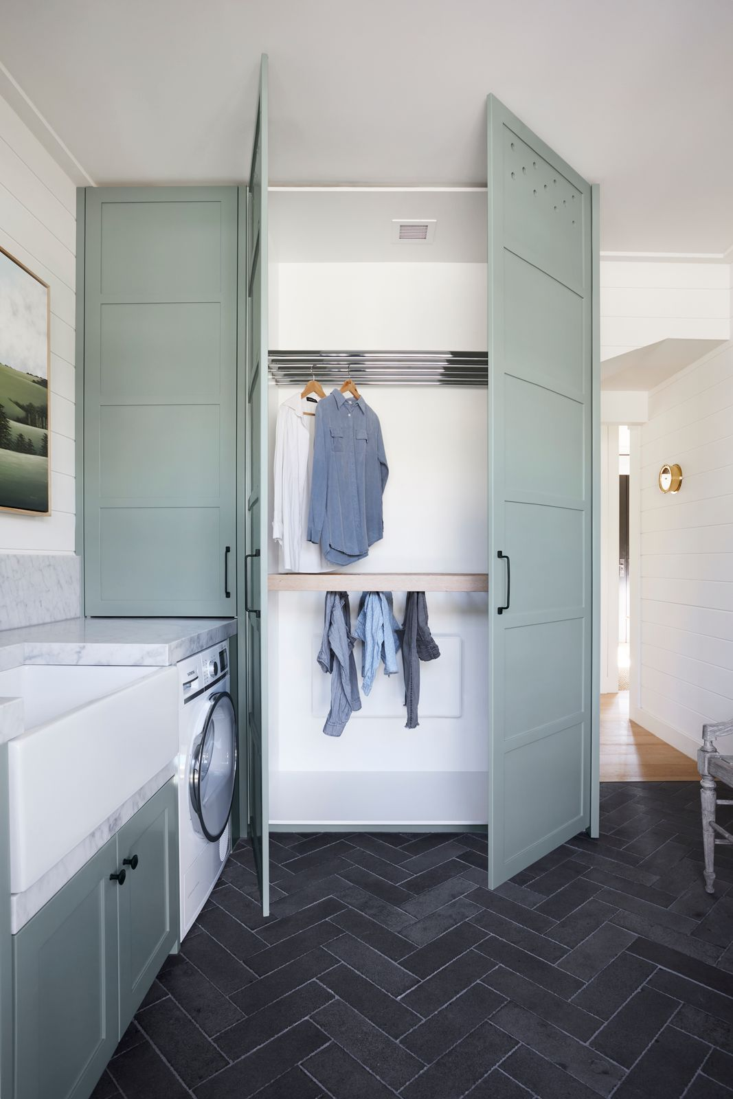 Green cabinetry in laundry mudroom room