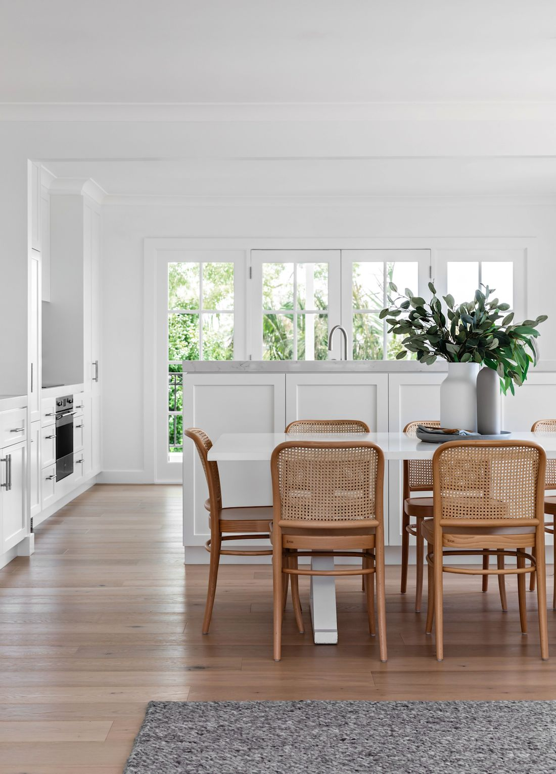 White kitchen with timber and rattan dining chairs