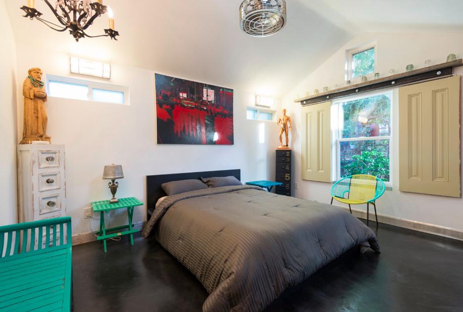 Eclectic bedroom with black concrete floors