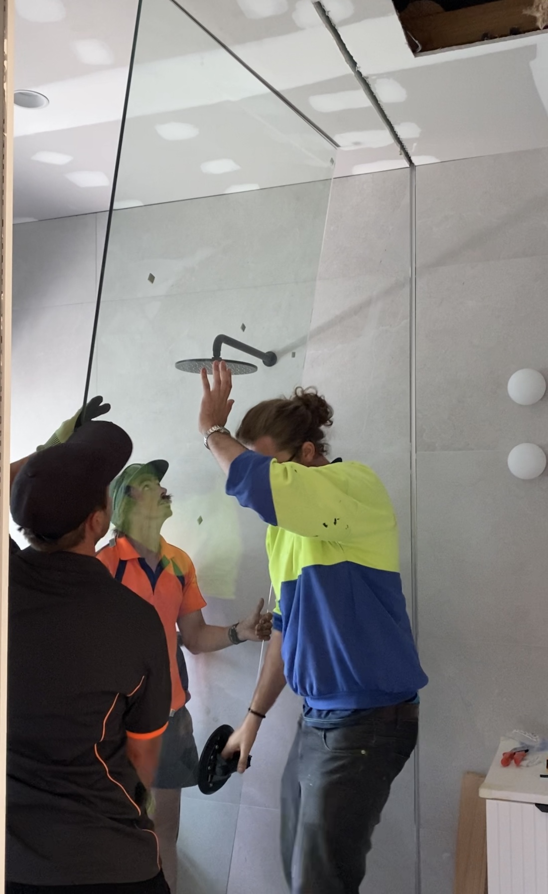 Glass screen being installed glass floor to ceiling shower screen