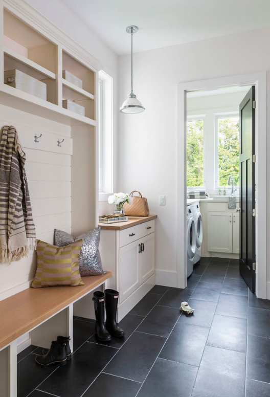 Laundry and mudroom with black ceramic floors