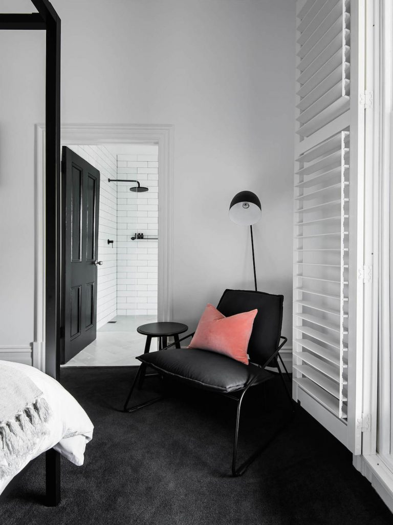 Black carpet in bedroom with four poster bed
