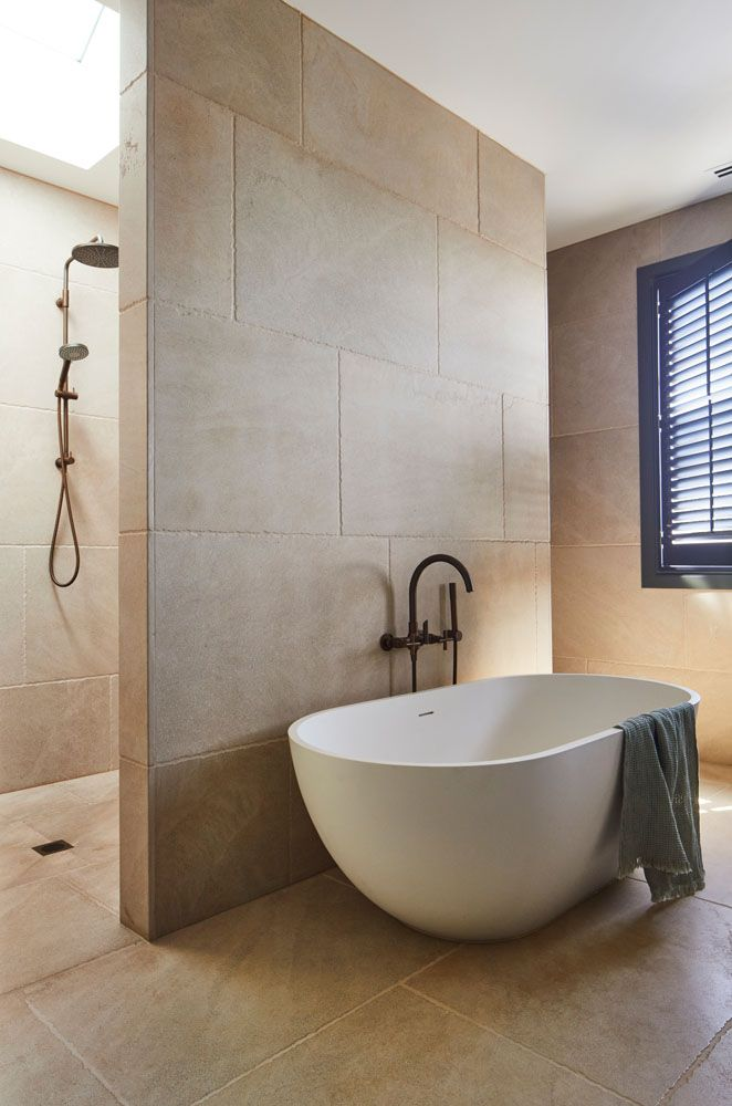 Blade wall in bathroom separating bath and shower