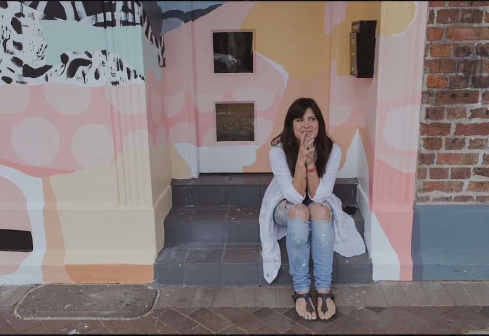 Kiasmin outside mural artwork she painted