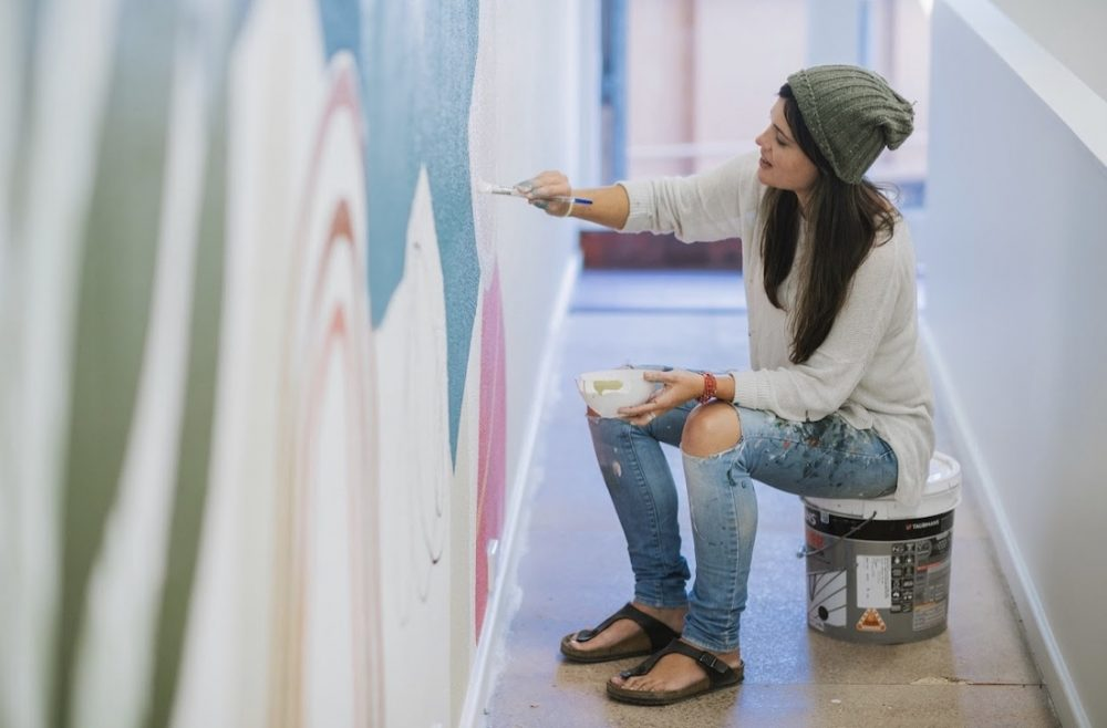 Painting a mural by artist Kiasmin