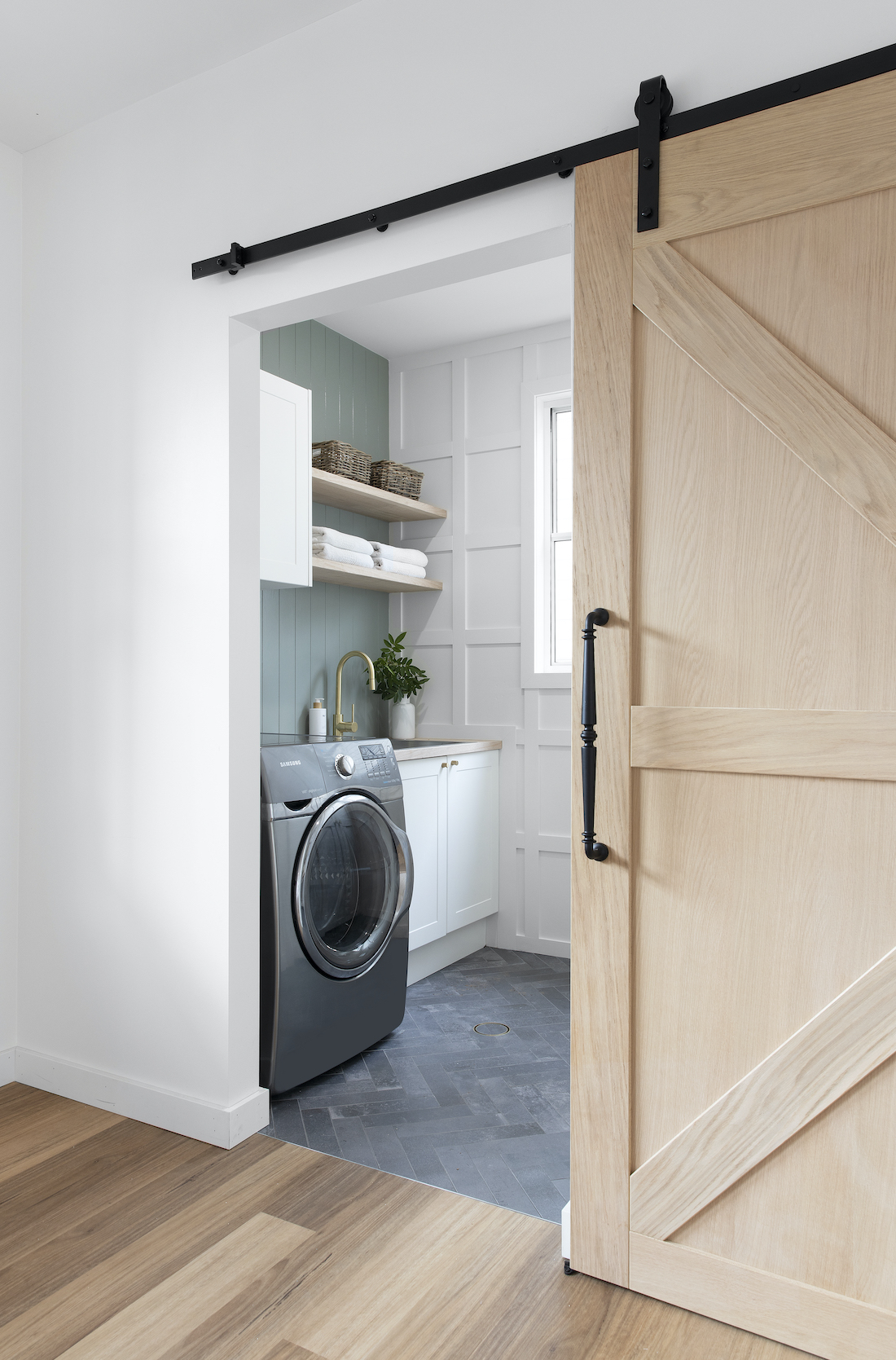 Laundry with panelling, green wall and sliding barn door