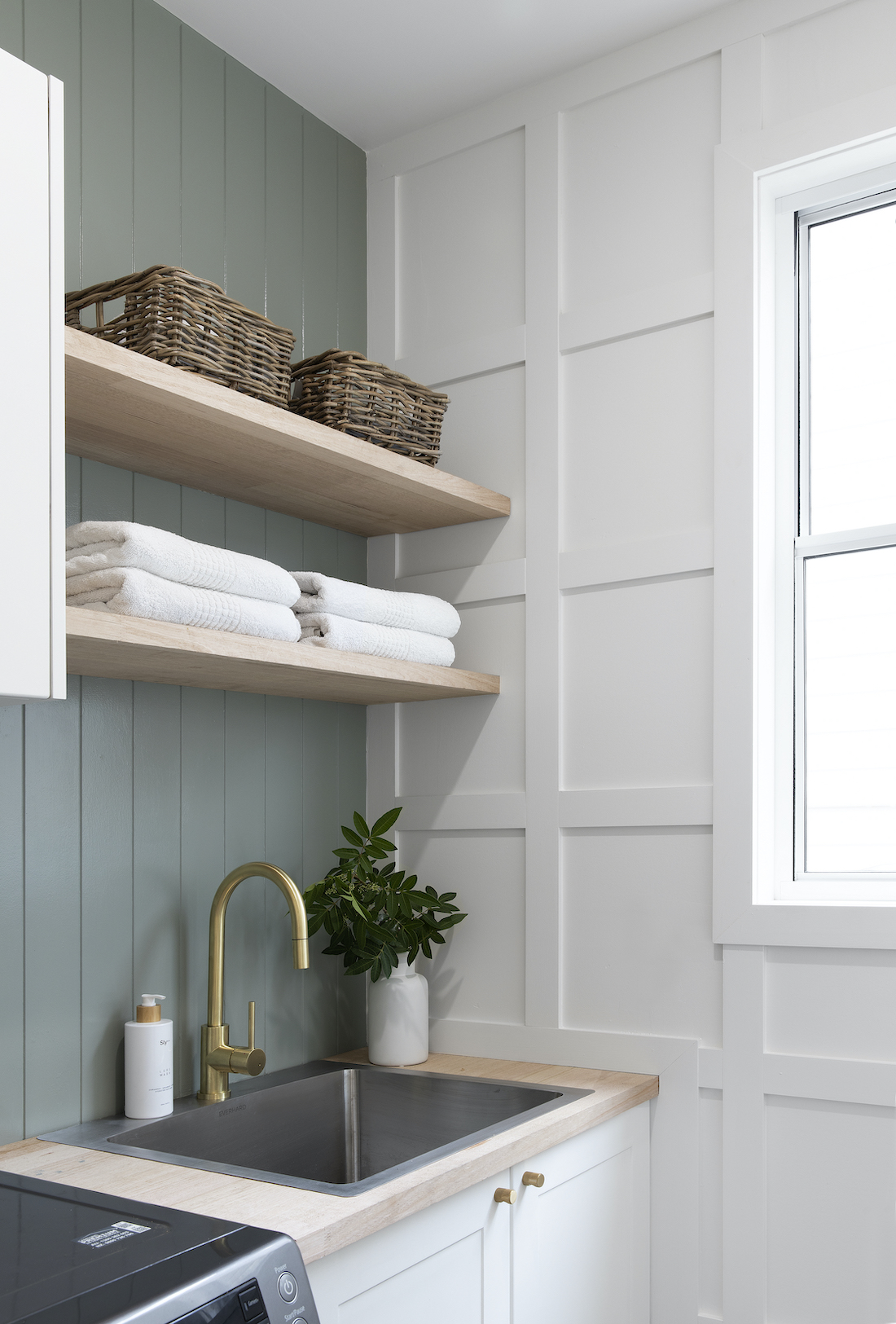 Green panelled wall in laundry with open shelving