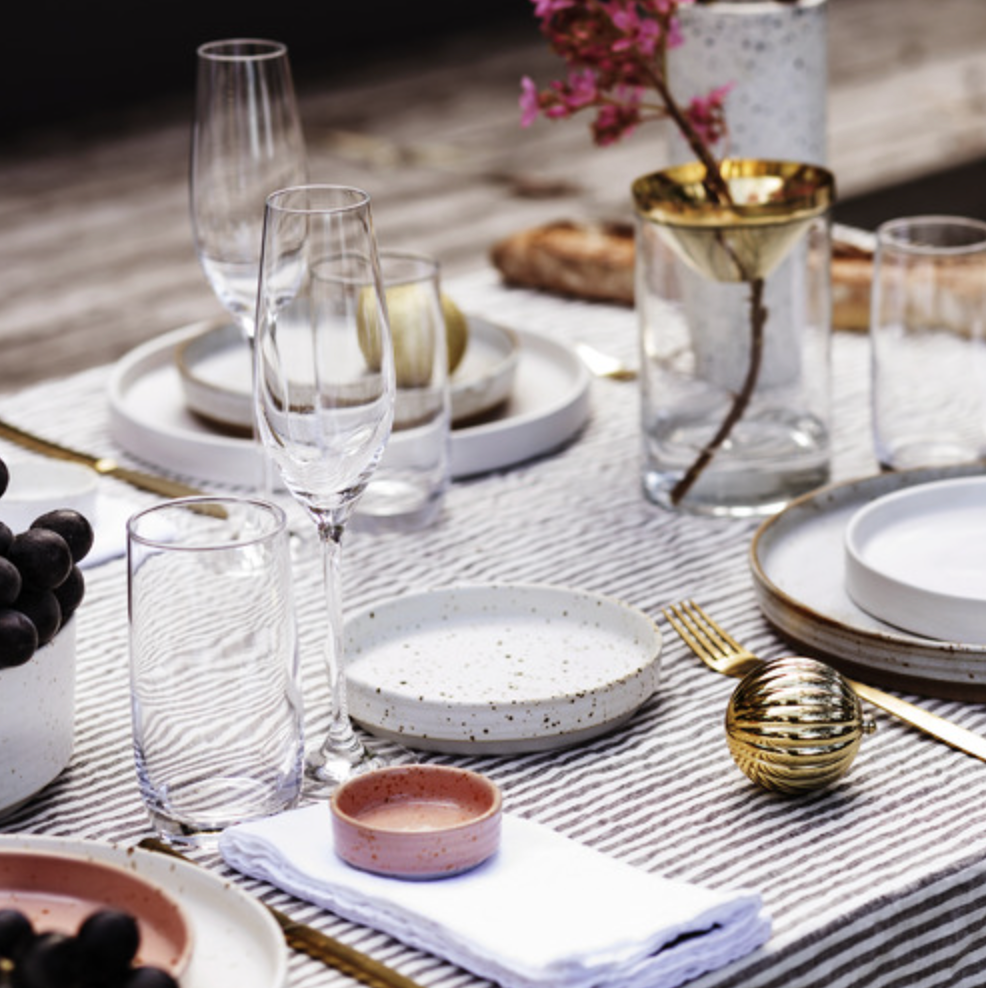 Dinner table set up with glassware and speckled dinner plate