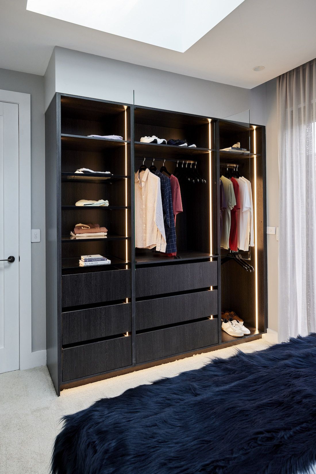 Dark timber built-in cabinetry with glass doors