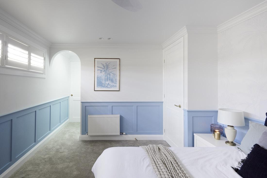 Blue wainscoating in Hamptons bedroom