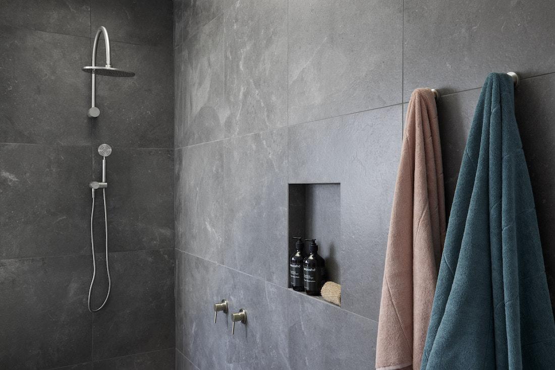 Dark tiled shower with shower niche