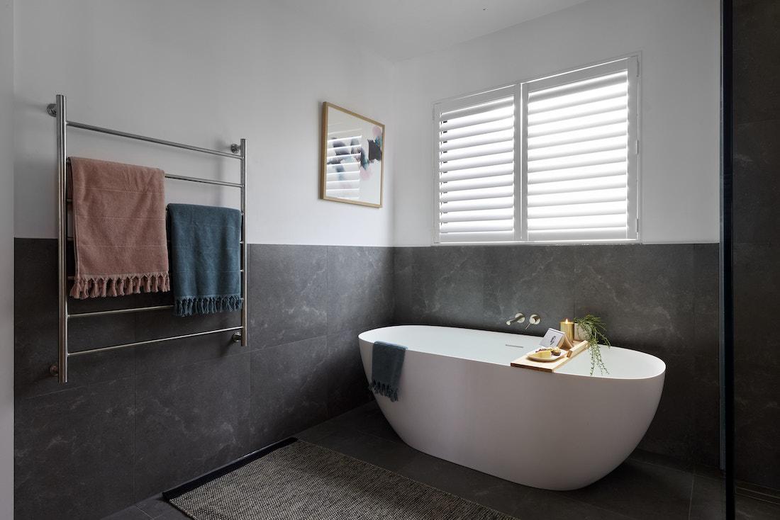 Large freestanding bath in dark toned bathroom